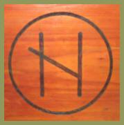Eine Binderune aus Naudiz und Hagal in Holz gebrannt und von einem Kreis umschlossen.