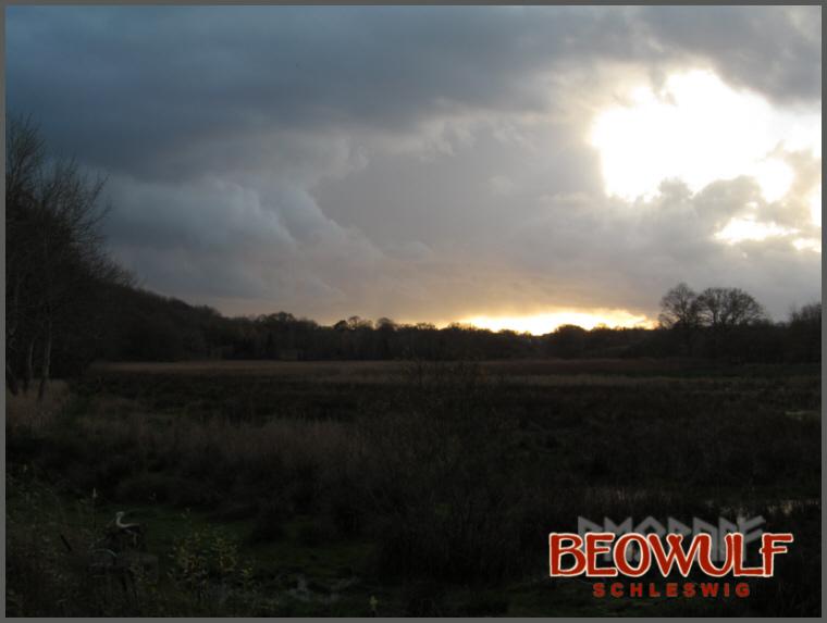 Dramatische Wolkenberge verdüstern Sonnenuntergangsstrahlen über einer feuchten Wiese, um die im Hintergrund Bäume stehen, die noch belaubt sind.