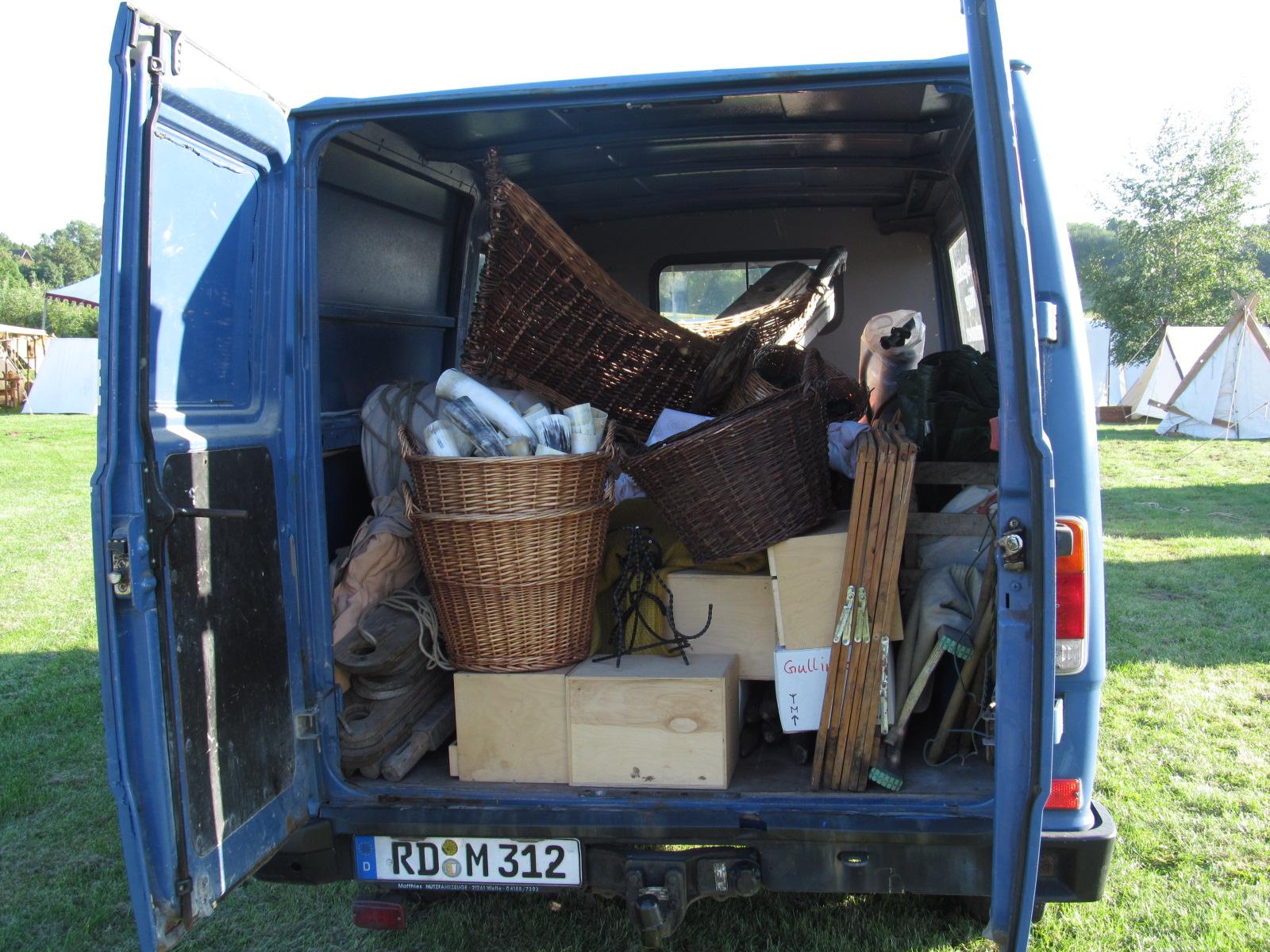Blick in die geöffneten Hintertüren unseres Transporters auf ein Chaos aus Körben mit und ohne Ware, Holzkisten, Tischböcken, Planen, hölzernen Zeltplanken, Seilen und Tüchern.