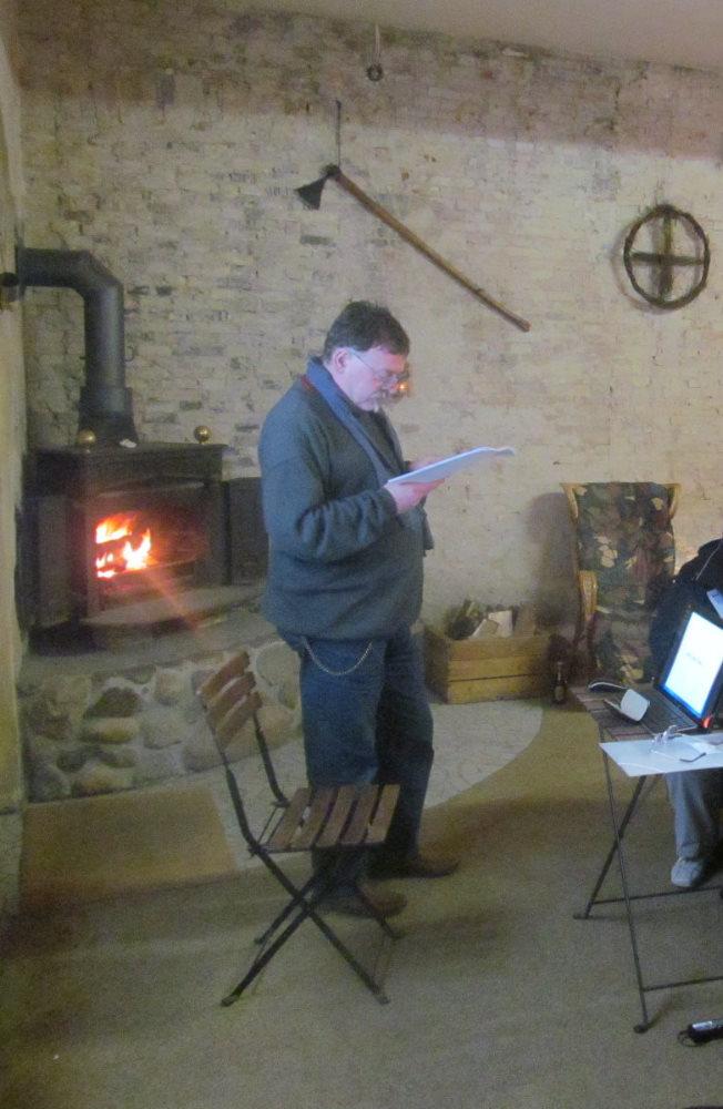 Gardenstone liest. Er steht dabei neben einem Ofen mit offenem Feuer, die Wand ist dekoriert mit einer Axt und einem Radkreuz aud Zweigen.
