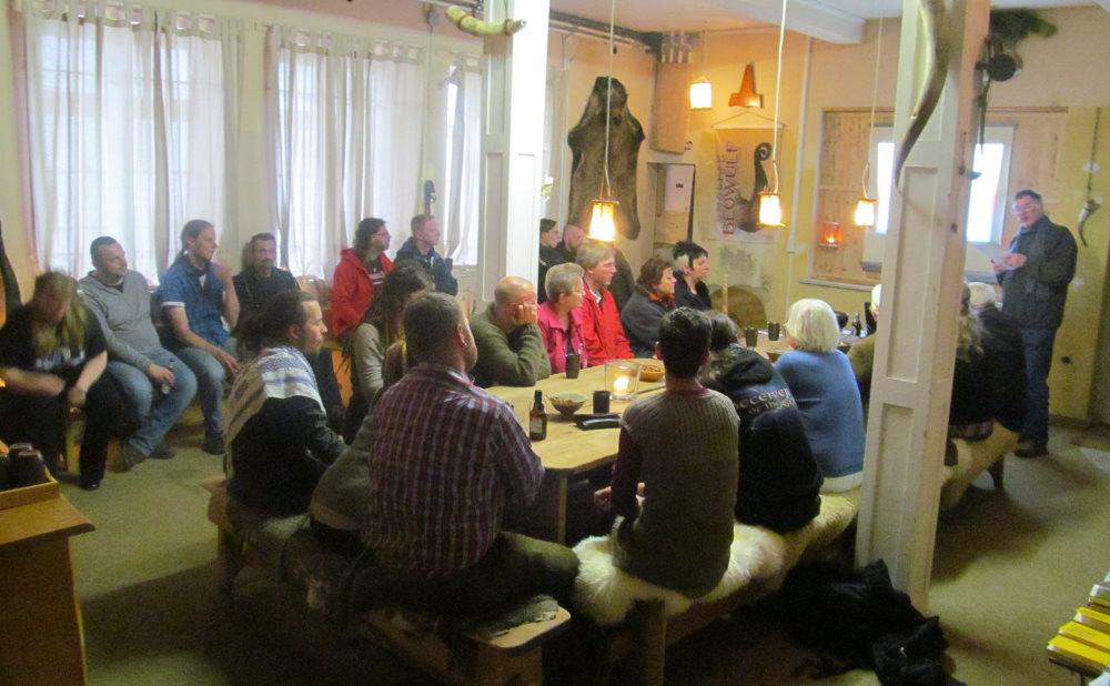 Blick auf mehrere Personen, die um eine Tafel und an der Wand entlang zuhörend sitzen.