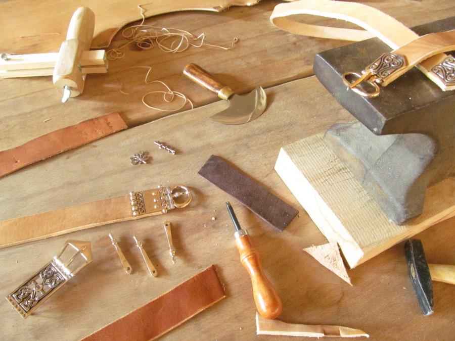 Neben dem Amboss liegen Werkzeuge zum Zschneiden und Vernieten der verschiedenen Gürtelbeschläge.