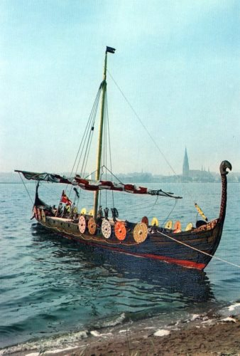 Wikingerschiff mit rundgeschwungenem Drachenkopf, Schilden an der Bordwand nd zusammengerolltem rot-weiß gestreiftem Segel.