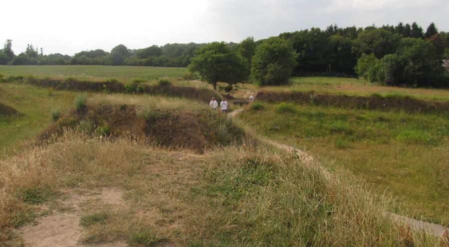 Blick von der Erthöhung der Schanze aus auf die flachere Seite, an der der Weg empor führt. Im Hintergrund sind Wiesen und Wäldchen sowie der Picknicktisch am Weg zu erkennen.