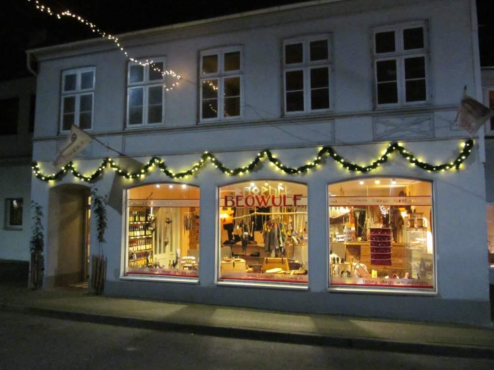 Die warm leuchtende Schaufensterfront unseres Ladens bei Dunkelheit mit Tannen-Licht-Girlande darüber.