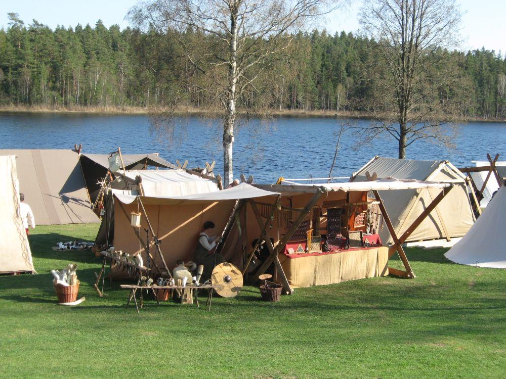 Am Ufer eines Sees sind verschiedenen Wikingerzelte aufgebaut. In der Mitte des Fotos ist unseres zu sehen, mit Schmuckpräsentation, Götterfiguren und Hörnern.