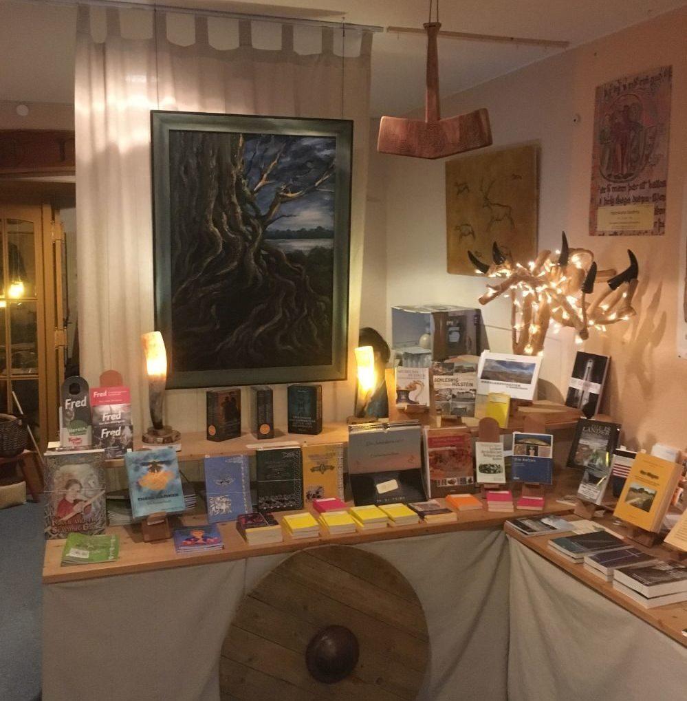 Über einem Büchertresen hängt ein Bild mit einer Malerei eines knorrig gewachsesen Baumes.