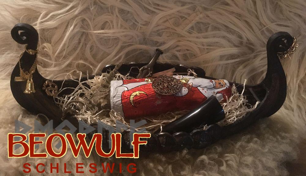 Eine kleines Modell eines Wikingerbootes, in dem ein Weihnachtsmann aus Schokolade liegt. Um ihn herum liegen ein kleines Schwert, ein kleines Trinkhorn und schildartige Gewandfibeln, die die Zusammenstellung wie eine Bootsbestattung für einen Kriegerfürsten in Miniatur aussehen lassen.