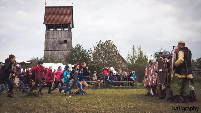 Eine wilde menge Kinder rennt auf eine Reihe Wikingerkrieger zu, die sich hinter ihren Schilden verstecken.