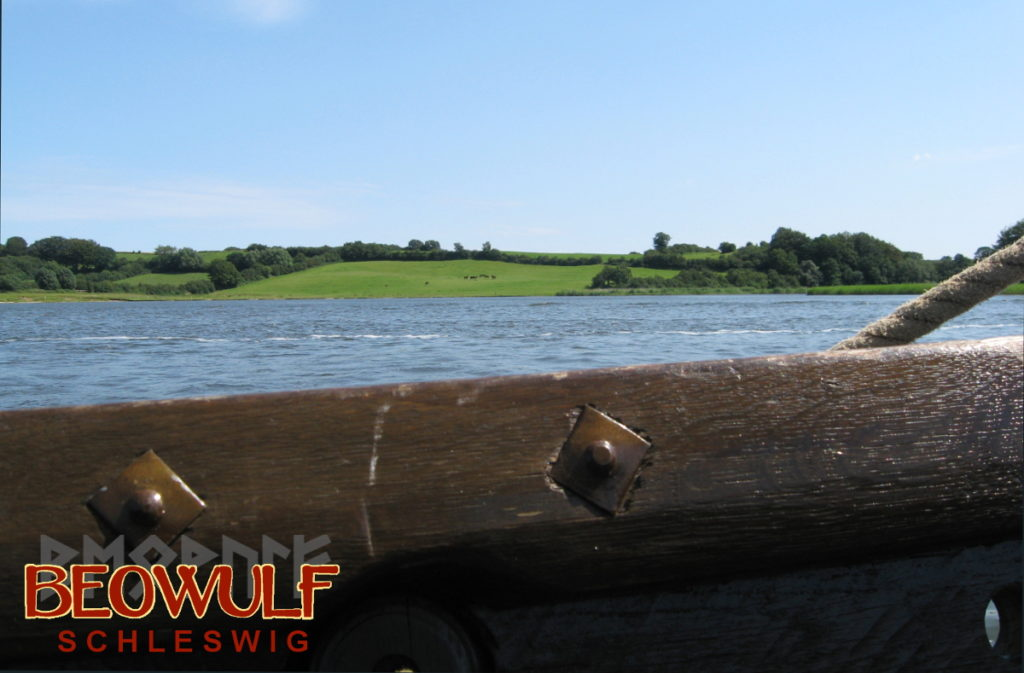 Das Ufer der Schlei von einem Wikingerschiff aus gesehen, dessen Bordwand mit Nieten unten am Bildrand zu sehen ist.