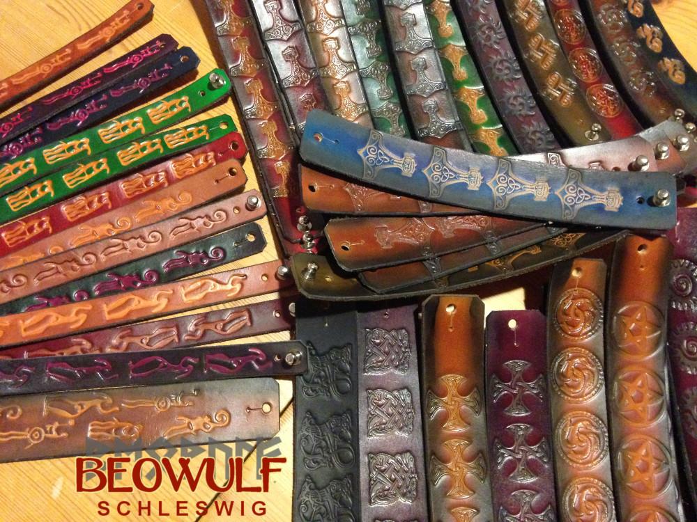 Viele Armbänder in verschiedenen Breiten und Einfärbungen, in die unterschiedliche Muster eingeprägt sind, liegen verteilt auf einem Holztisch.