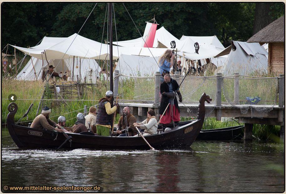Ein Boot slawischer Bauart hält, mit Kriegern bemannt, auf einen Anleger zu. Im Hinmtergrund sind Zelte aufgebaut.