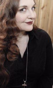 Eine Aufnahme von Luci van Org, auf der sie einen Thorshammer an einer langen Halskette trägt.