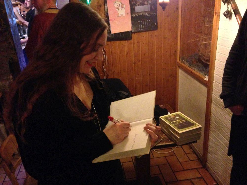 Luci schreibt auf die erste Seite eines Buches eine Widmung. Hinter ihr liegen weitere Bücher auf einem Tisch.