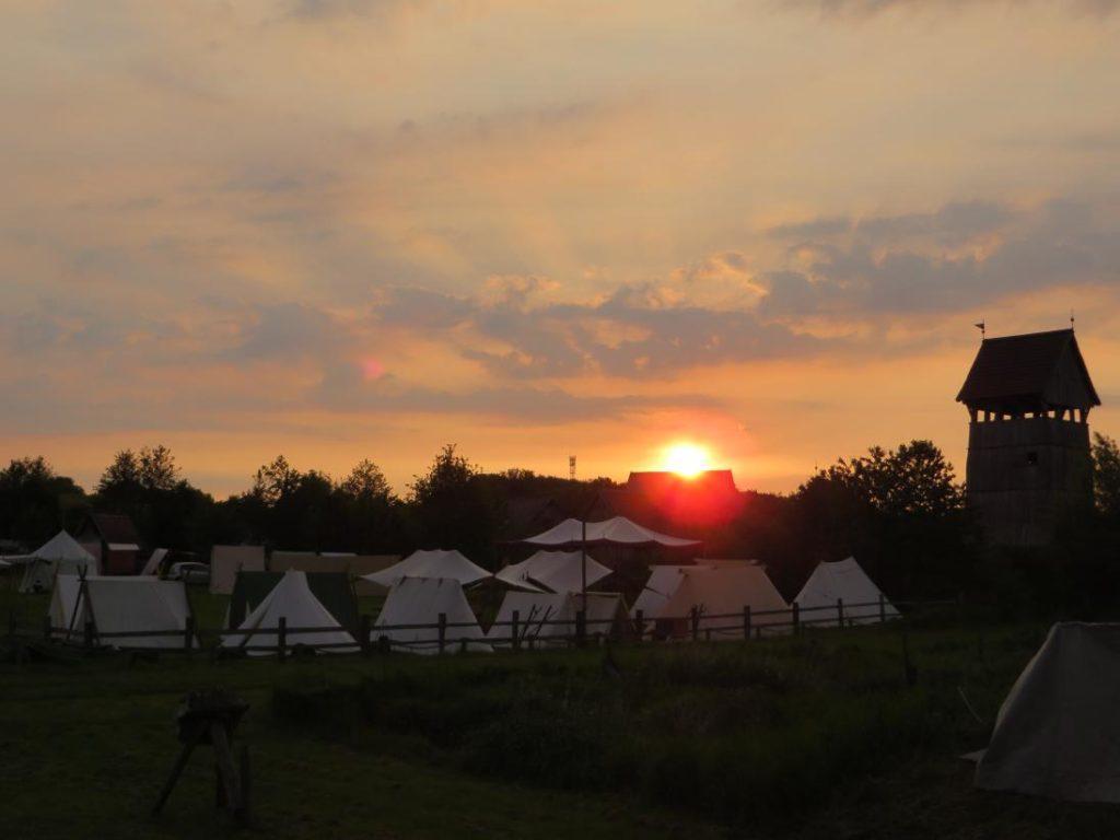 Sonnenuntergang über einer Wise, auf der viele Wikingerzelte stehen, rechts daneben der große Holzturm der Burg.