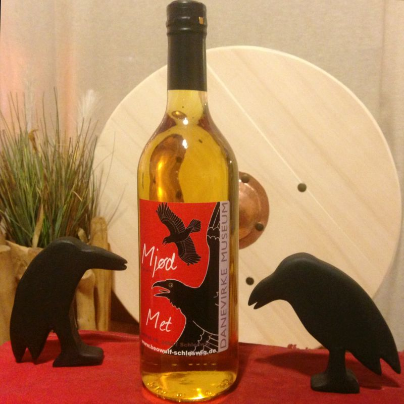 """Eine Flasche Met mit Etikett, das Elemente des Logos des Museums aufgenommen hat: Roter Hintergrund, zwei schwarze Raben im Flug, den Museumsnamen in Grautönen und das Wort """"Met"""" in beiden Sprachen."""