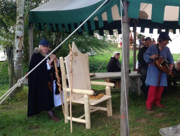 Ein aus hellen Holzbalken zusammengebauter großer Holzstuhl mit Lehne. Diese ist schwungförmig verziert und an ihr ist ein Metallschild mit den Namen der Sieger des Wettbewerbs befestigt.