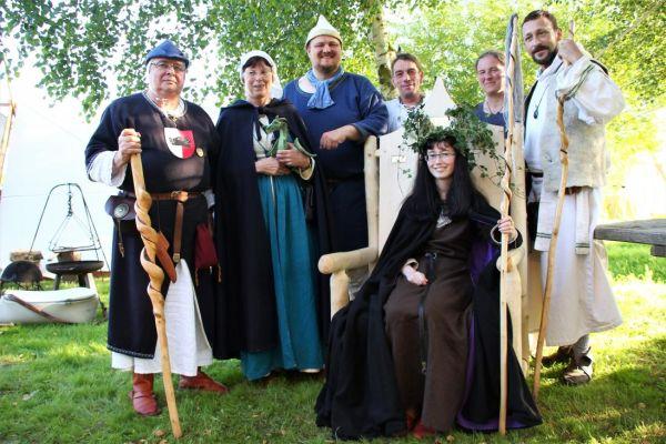Vier Männer ud zwei Frauen stehen hinter dem Thron, auf dem eine junge Fraus sitzt.