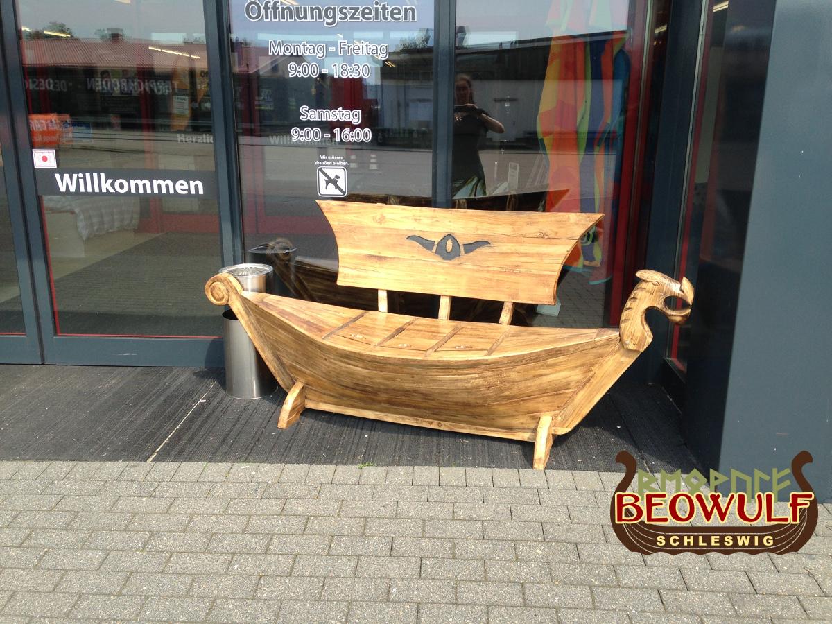 Vor der modernen Glastür eines Geschäftes steht eine Holzbank in Form eines Wikingerschiffes mit Drachenkopf am Bug. Das Segel ist die Lehne.