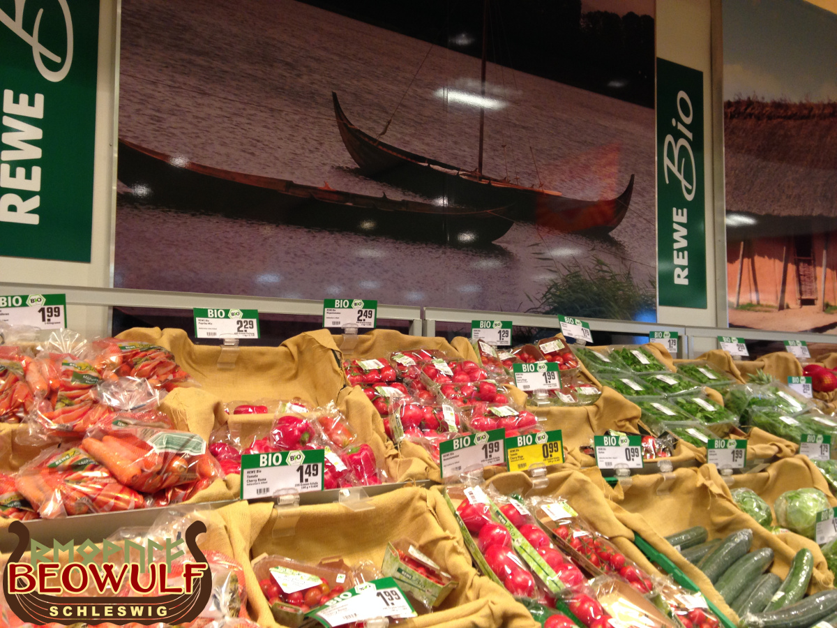 Über einer Gemüse-Auslage vor einer Wand hängt ein großes Foto mit zwei Wikingerbooten darauf.