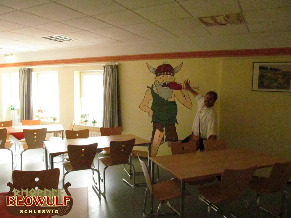 Die Wandbemalung in einem Speisesaal in der Jugendherberge Borgwedel zeigt einen hörnerbehelmten Wikinger, der in eine Fleischkeule beißt.