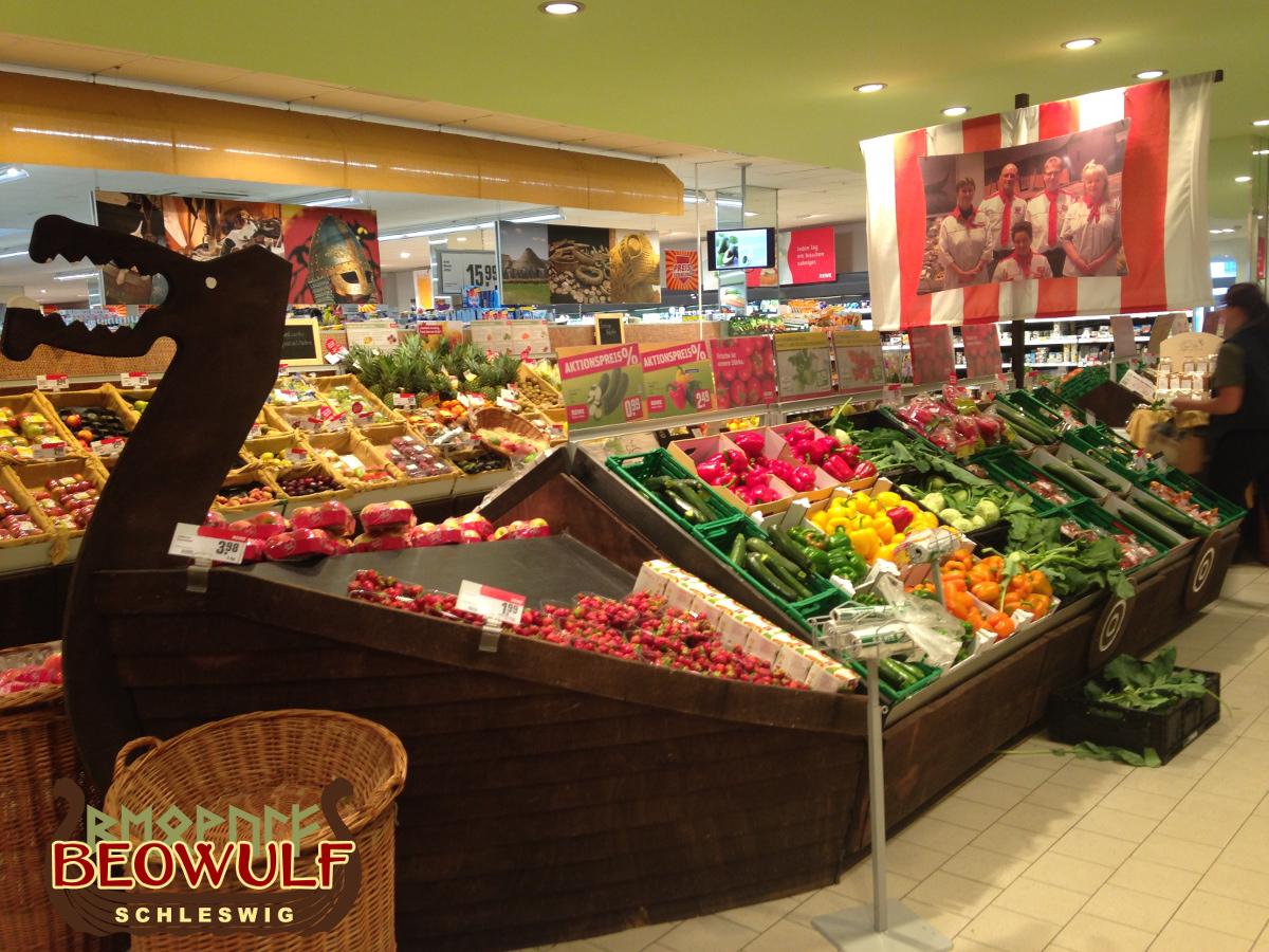 Die langgestreckte, freistehende Gemüsetheke in einem Supermarkt ist wie ein Wikingerboot gestaltet, aus Holzplanken mit Drachenkopf am Bug.