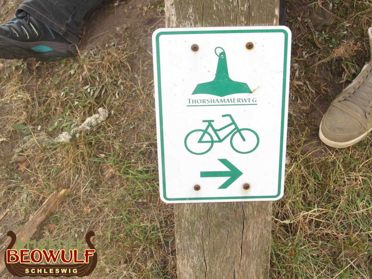"""An einem Holzpfosten ist eine Wegemarkierung für den Ragweg """"Thorshammerweg"""", auf dem Schild ist aßer dem Namen und der Richtungsanzeige ein Rad und ein Thorshammer-Anhänger abgebildet."""
