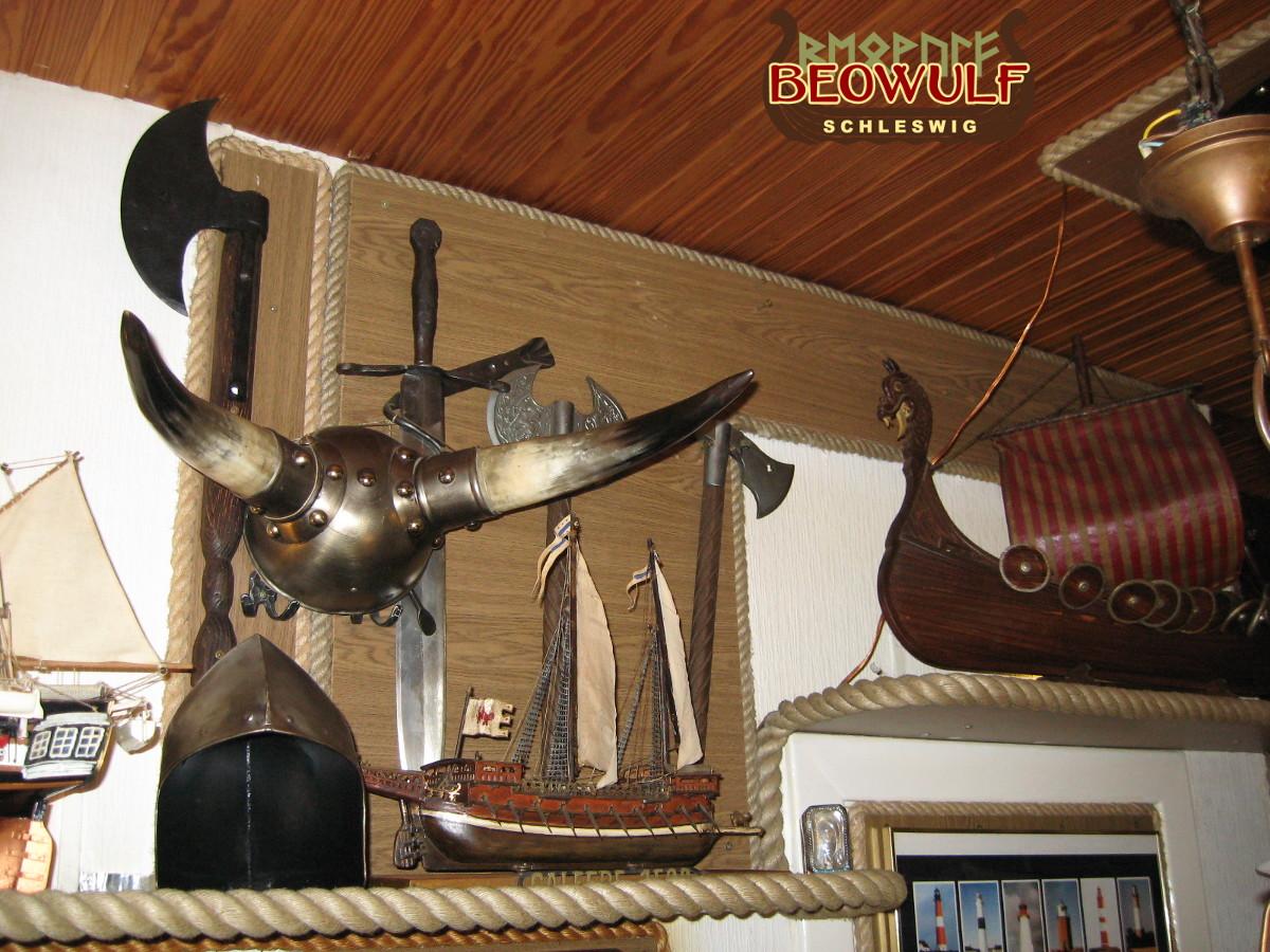 Auf einem Regal und an der Wand stehen und hängen Hörnerhelm, Helm, Wikingerschiff, Deko-Schwert und -Axt neben Leuchtturmnippes und Koggenmodell.