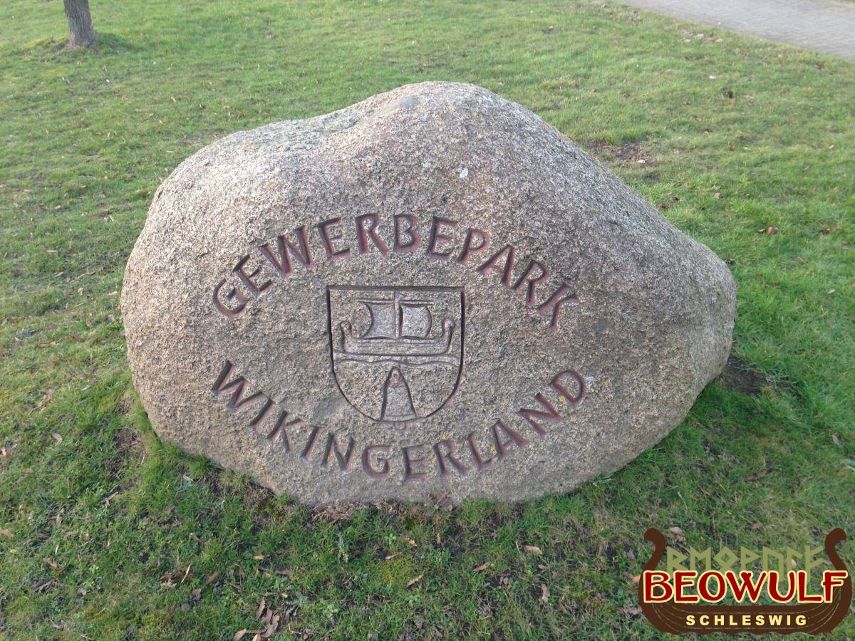 """Ein ca. oberschenkelhoher Feldstein, auf dem das Gemeindewappen eingemeißelt ist, welches vom Schriftzug """"Gewerbegebiet Wikingerland"""" umgeben ist."""