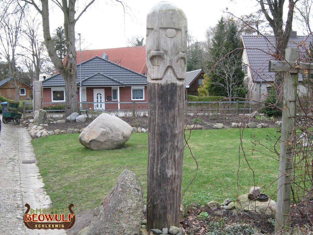 In einem Vorgartenbeet steht ein mannshoher Holzpfahl, der am oberen Ende als vierseitiges Gesicht ausgearbeitet ist.