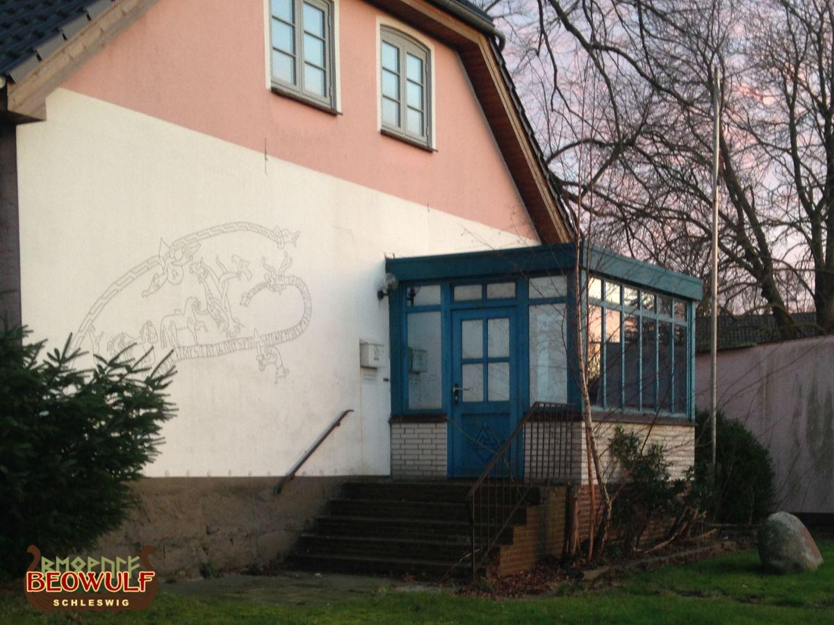 Ein gemaltes Motiv an einer Hauswand, eine beschnitzte Türfüllung und ein Vorgartenstein - alles in Wikingerstil.
