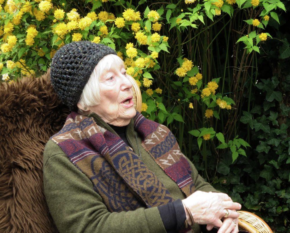 Eine weißhaarige Frau, die einen Schal mit Runen und Flechtmuster trägt, sitzt in einem Stuhl und erzählt.